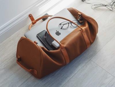 Reiserücktrittsversicherung nach Buchung: Gepackte Ledertasche, MacBook, iPhone und Kopfhörer liegen auf dem Holzboden