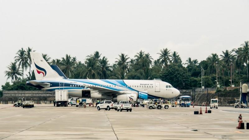 Flugzeug von Bagkok Air steht am Flughafen mit Palmen im Hintergrund