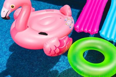 Bunte Luftmatratzen und Schwimmringe im Pool