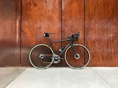 Schönes Rennrad vor einer dunkelbraunen Holzwand