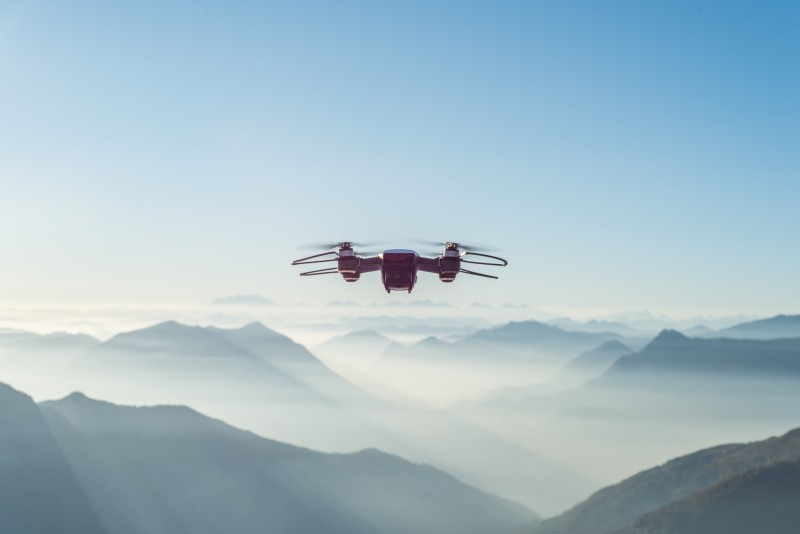 Drohne am strahlend blauen Himmel, im Hintergrund Berge