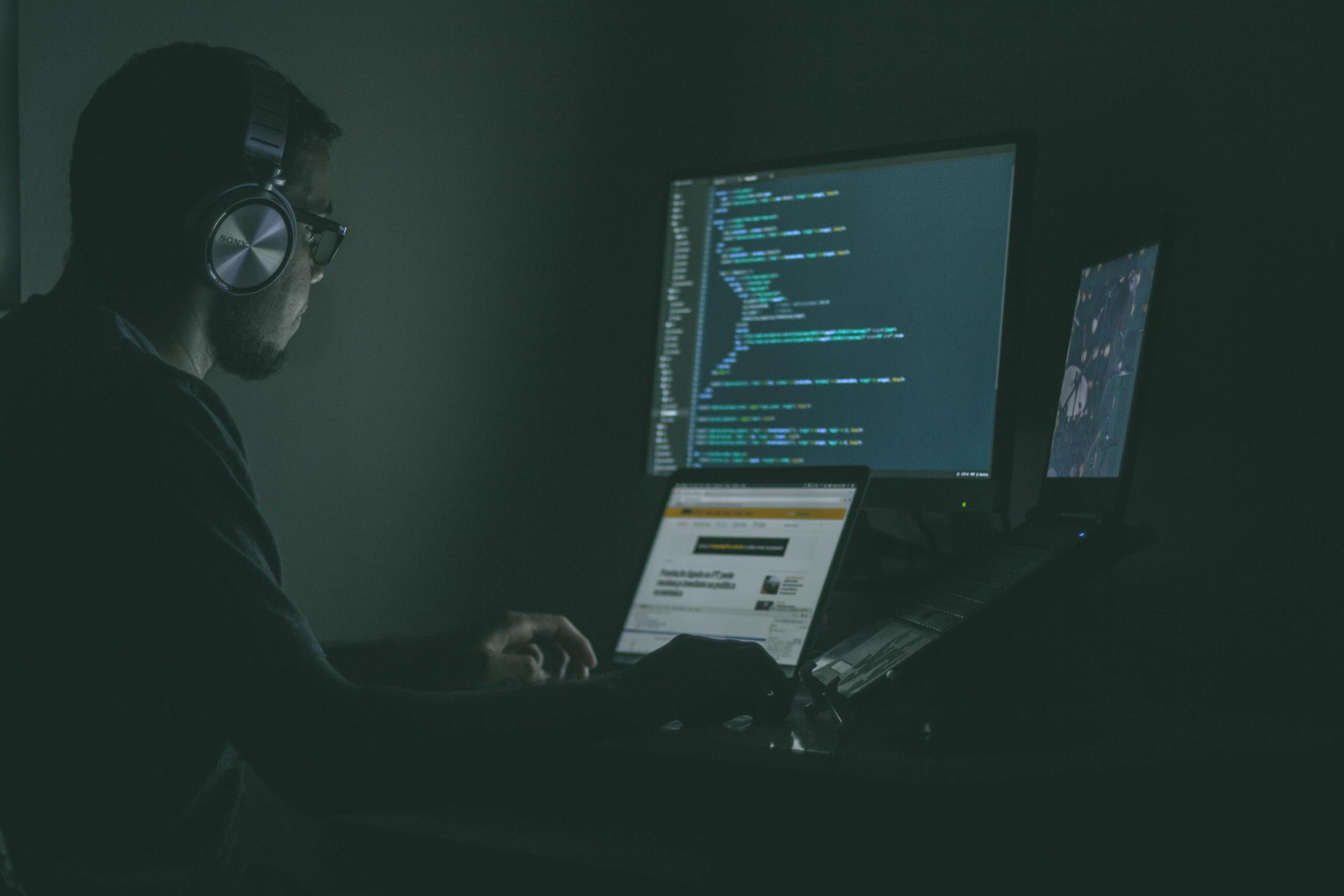 Mann mit Kopfhörern am Programmieren