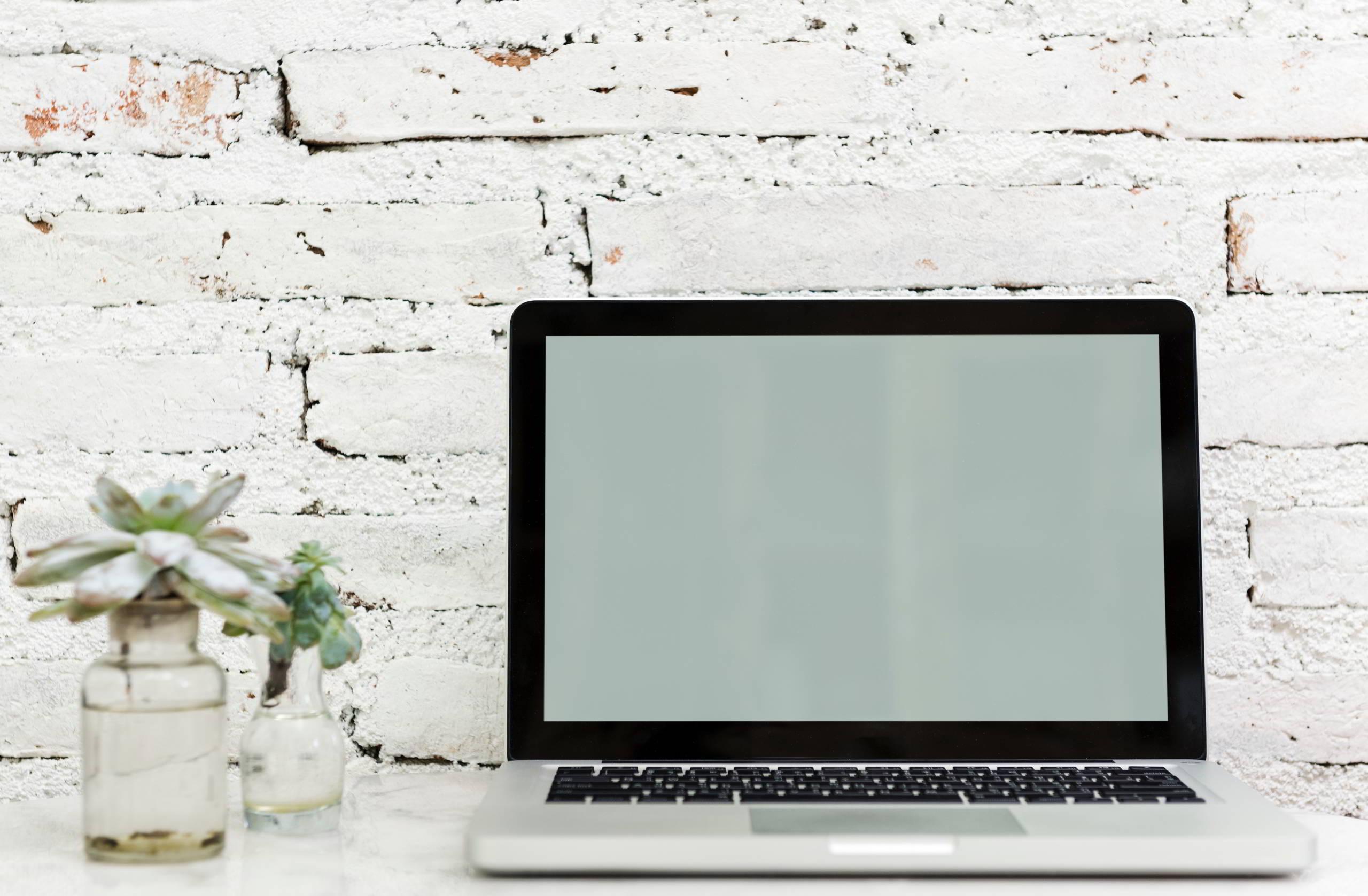 MacBook vor weißer Wand