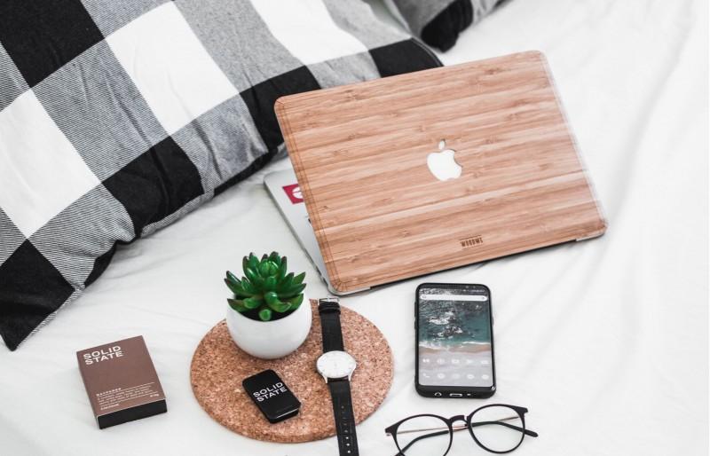 Android-Smartphone und Apple-Lapotop auf einem Bett