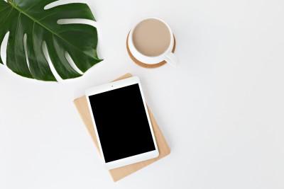Tablet liegt aus einem hellem Tisch, eine Tasse Cafe steht daneben.