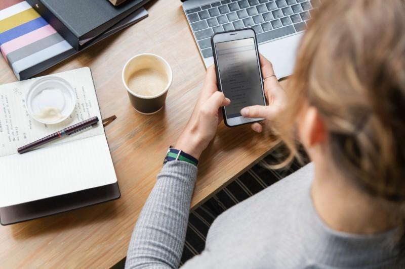 Frau am Schreibtisch mit Smartphone und Laptop