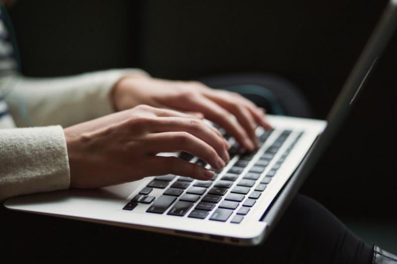 Frau tippt auf einem MacBook