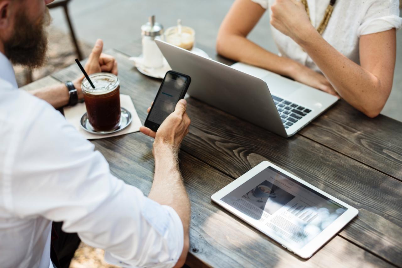 Zwei Personen an einem Tisch mit einem Laptop, Tablet und Smartphone