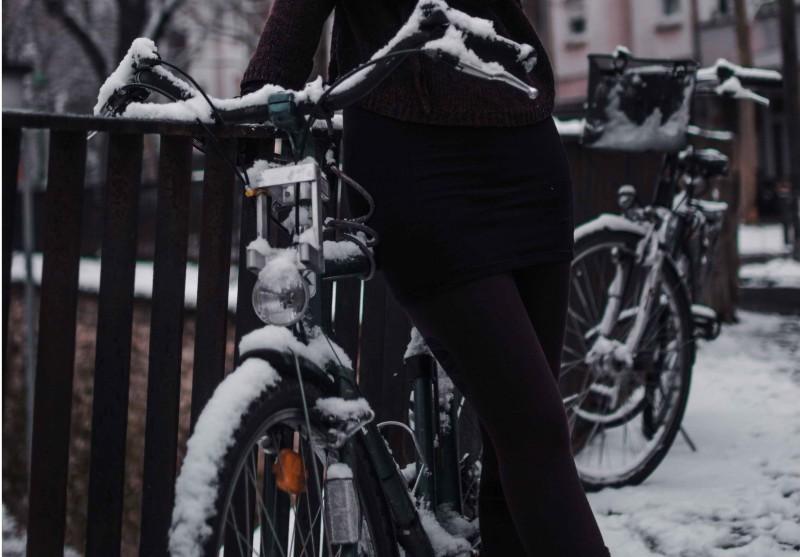 Fahrrad fahren im Winter: Was solltest Du beachten: Schneebedecktes Fahrrad steht an einem Geländer.