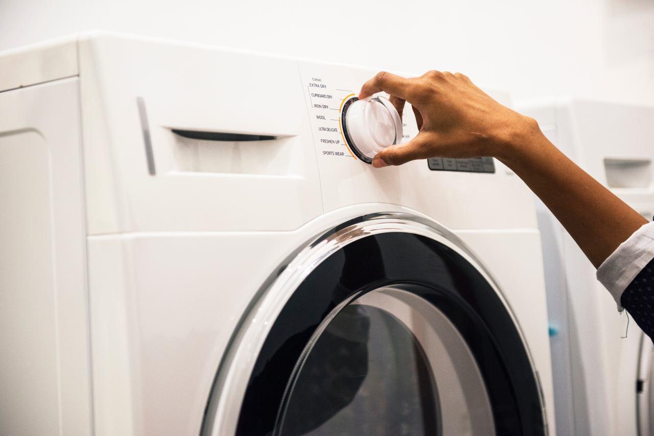 Haushaltsgeräte: Herstellergarantie vs. separate Elektronikversicherung:Waschmaschine mit Hand am Drehknopf für Einstellungen des Waschganges.