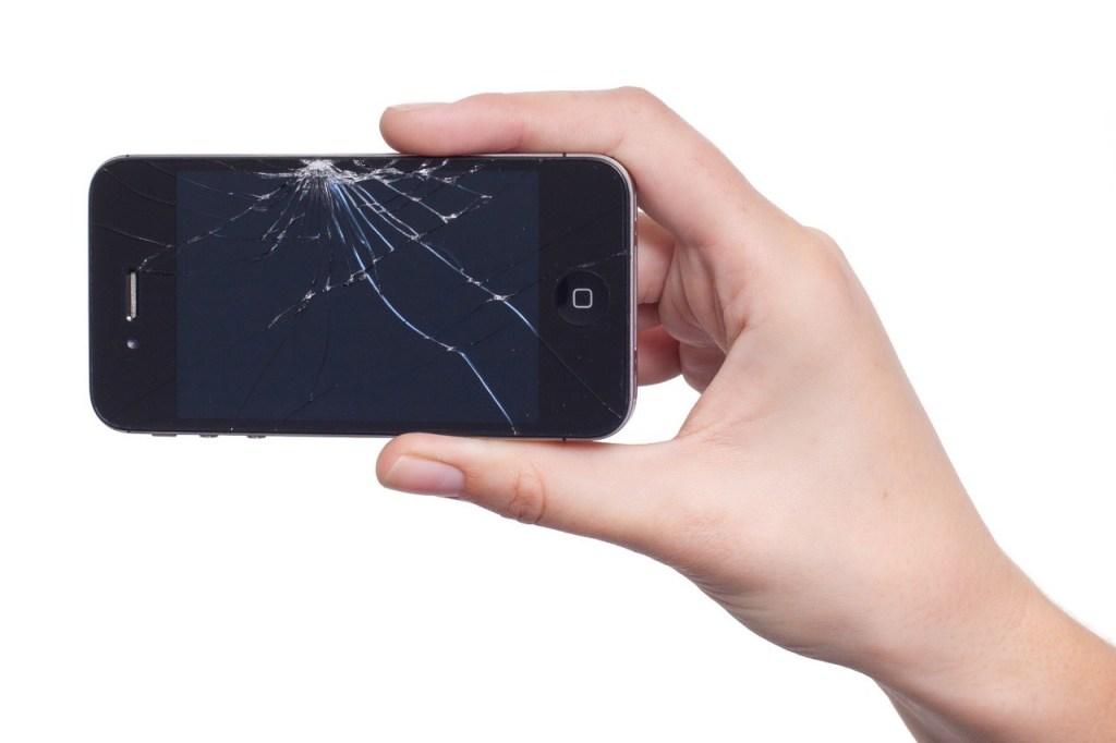 Displayreparatur: Eine Hand hält ein iPhone mit zersplittertem Display in der Hand