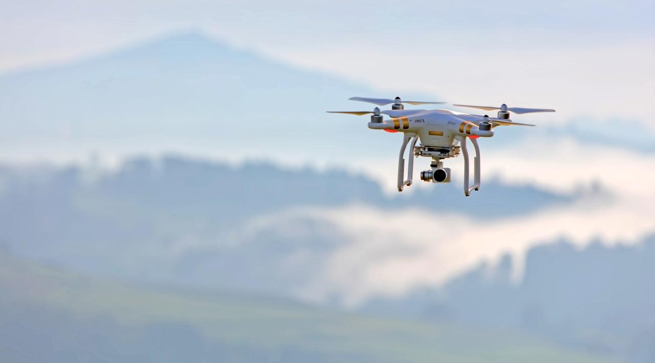 Drohne fliegt vor den Bergen.