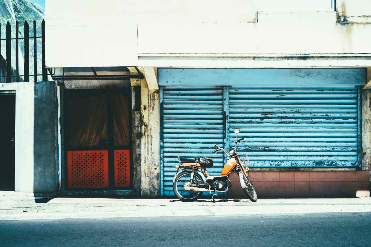 Moped steht vor einer Wand.