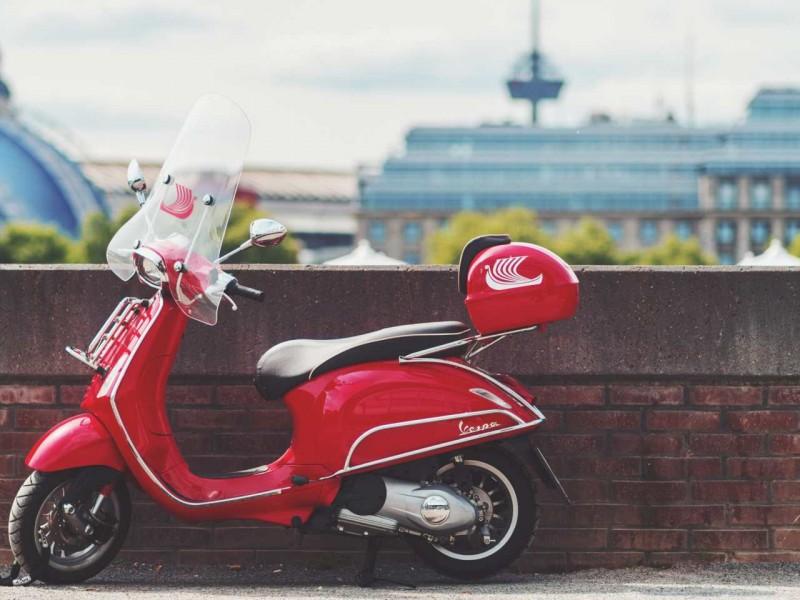Motorroller steht vor einer Wand in Köln.