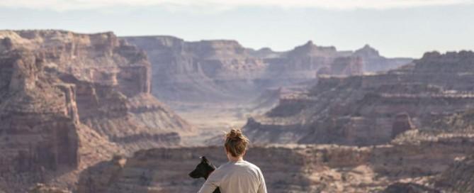 Hund sitzt mit Frau vor dem Grand Canyon