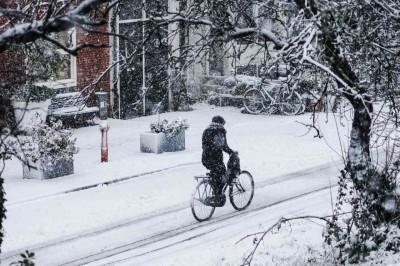 Frau auf Fahrrad fährt durch den Schnee.