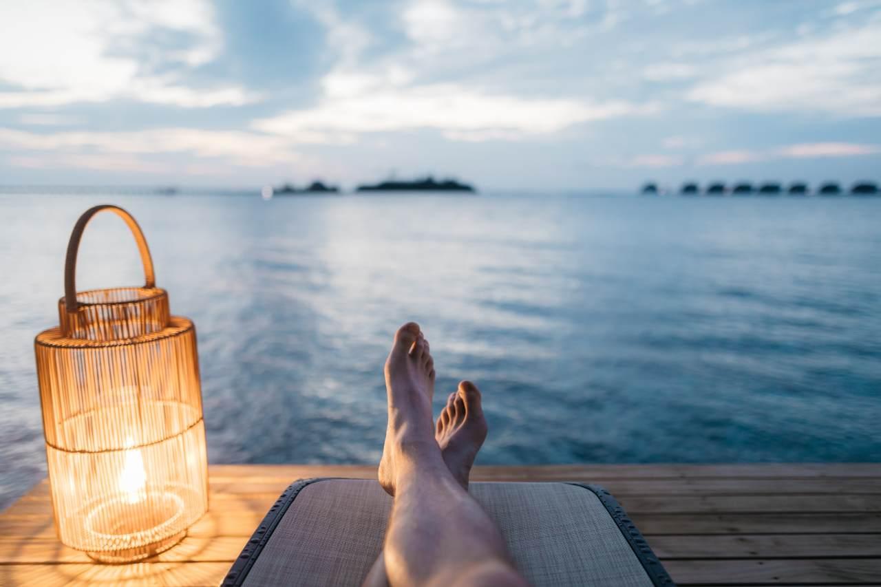 Person liegt auf einer liege am Meer.