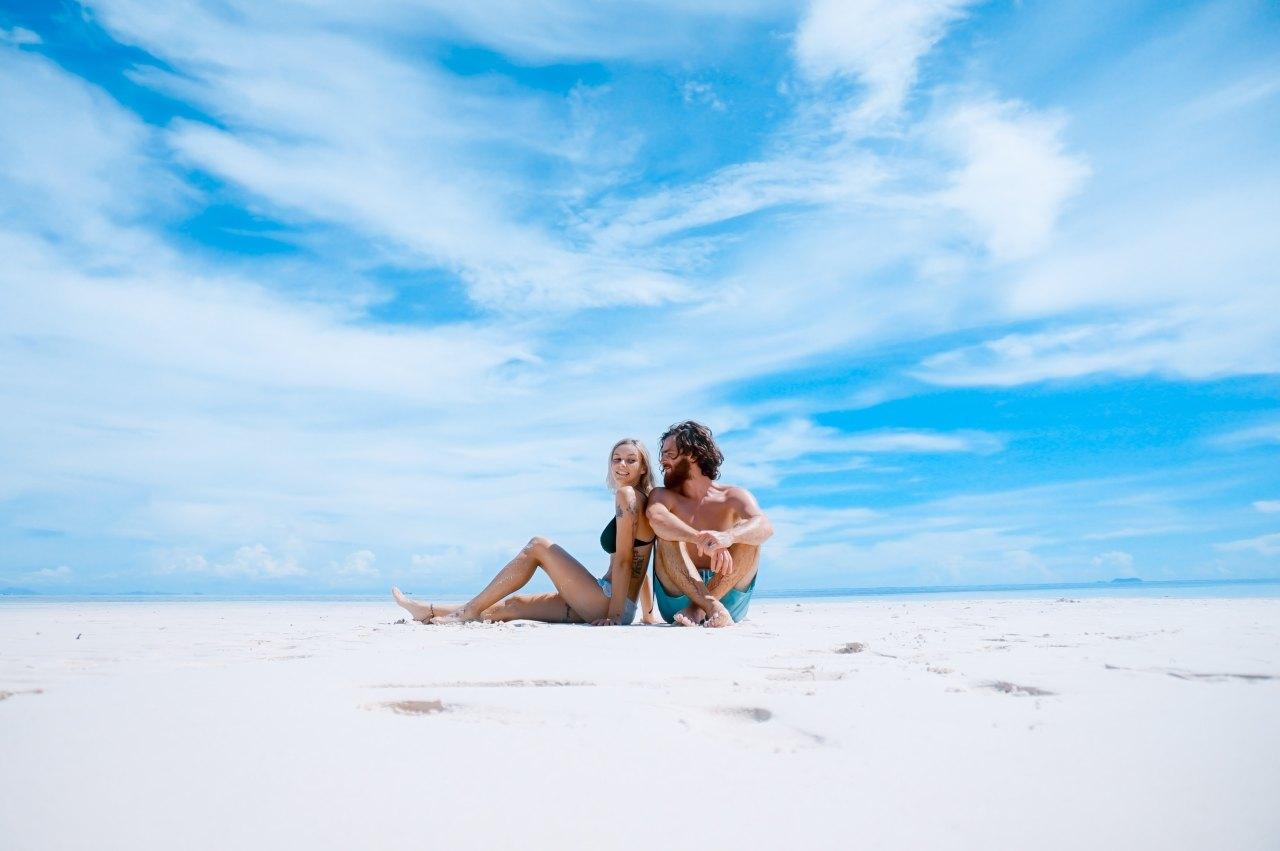 Pärchen sitzt am Strand im Sand.